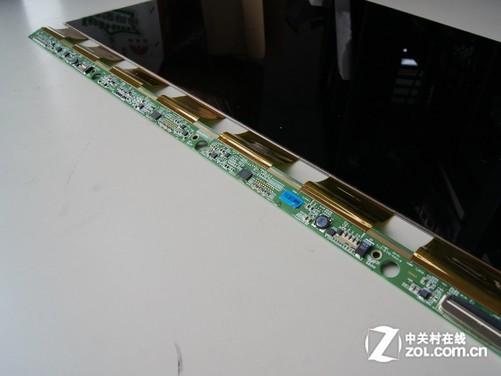 按照上面图片的步骤和介绍,一步一步的进行拆卸,我们就可以看到三星S23A950D液晶显示器完整的液晶面板控制电路。与我们以往拆解的几款LED背光液晶显示器有所不同的是,三星S23A950D除了在液晶面板分子层底部连接了一块控制电路板之外,在两侧分别设计了四个小块的软性电路板,每个电路板上有一个类似于芯片的物体,这个设计也是我们首次看到,我们猜测它可能是实现3D画面显示时的重要部件。